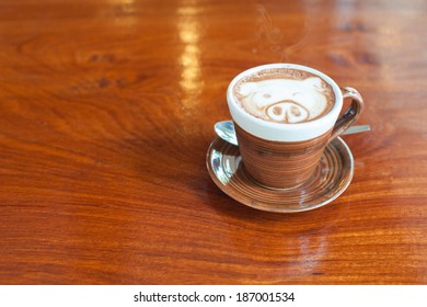 A cup of hot coffee with cute pig pattern on wooden table