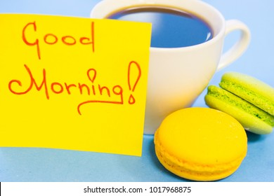 A cup of hot coffee, delicious macaroons and Good Morning yellow sticker note on a blue background