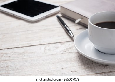 Cup of hot coffee and diary on wood table background