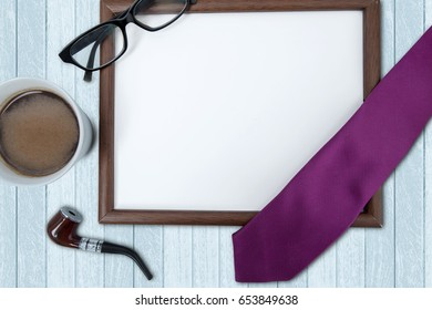 Cup of hot coffee with an empty frame, tie, smoke pipe, and glasses on the wooden table, concept of father's day