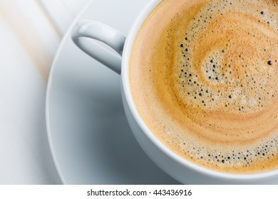 A cup of hot coffee with foam on a white wooden table
