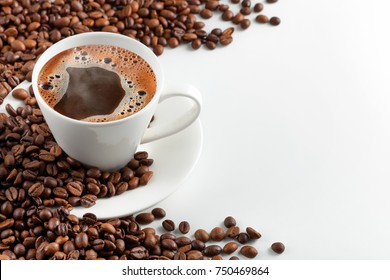 A cup of hot coffee with foam in a scattering of coffee beans on a white background