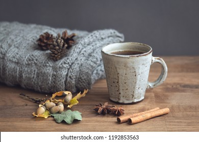 Cup of hot coffee with foam in the shape of a heart on a rustic wood table background wrapped in warm knit wool scarf. View from the side. space for text.  Holidays and events. Winter background