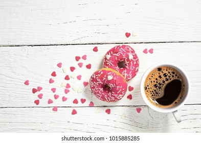 Cup of hot coffee and glazed pink donuts with sprinkles on white wooden table, top view