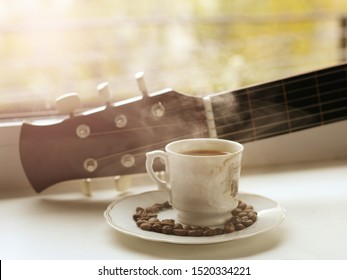 A Cup of hot coffee and a guitar on a Sunny window, sunlight