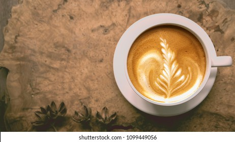 A cup of hot coffee ,latte art on wood table in morning, Coffee with a pattern of milk in white cup.