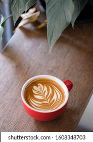 cup of hot coffee latte art on wood table background