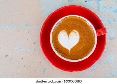 cup of hot coffee latte art heart on the table, coffee top view