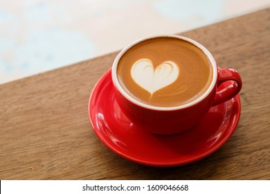 cup of hot coffee latte art heart on wooden table