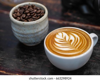 cup of hot coffee latte ,beautiful latte art and cup of roasted coffee beans on dark wooden background