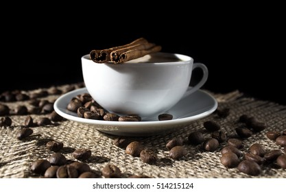 cup of hot coffee with milk and cinnamon sticks and coffee beans on a napkin of burlap