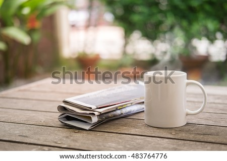 Cup of hot coffee and newspaper on wooden table in garden morning