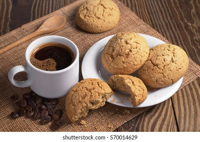Cup of hot coffee and oatmeal cookies in plate on rustic wooden table