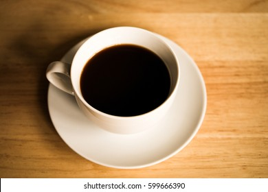 Cup of hot coffee on brown wooden table, homemade coffee for relaxing at home