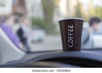 Cup of hot coffee on car console. Blurred background.