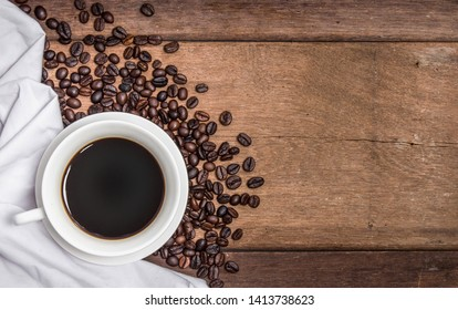 A cup of hot coffee on a folded white cloth and an old wooden table