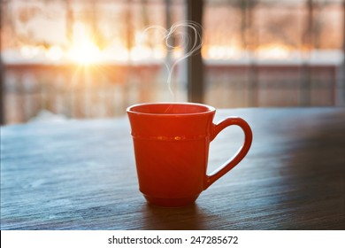 a cup of hot coffee on a rustic table against the morning rising sun