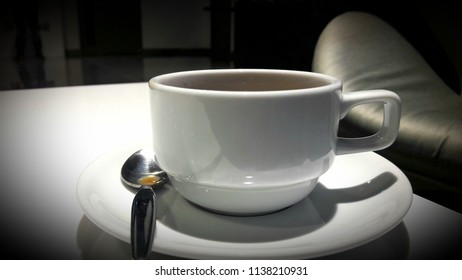 Cup of hot coffee on white table on break time, black background.