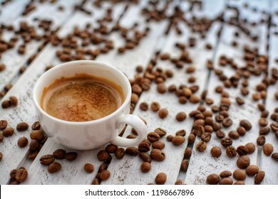 Cup of hot coffee on the white table with coffee beans