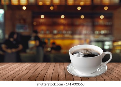 Cup of hot coffee on wood table in cafe with people.