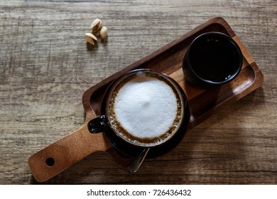 Cup of hot coffee on wooden table. Capuchino coffee