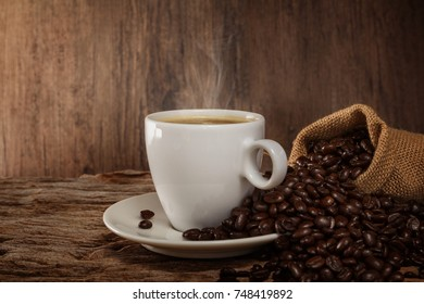 A cup of hot coffee on a wooden table with roasted coffee beans
