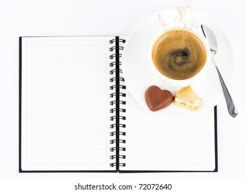 Cup of hot coffee and open note book on white background