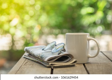 Cup of hot coffee, reading glasses and newspaper on wooden table in the garden morning