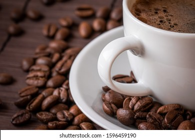Cup of hot coffee and a scattering of coffee beans on a bamboo serving napkin.