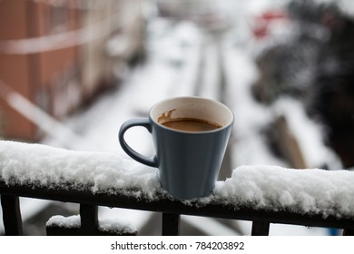 Cup of hot coffee in snow at the balcony with city view