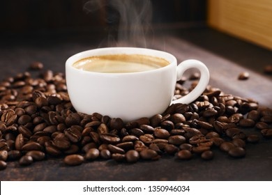Cup of hot coffee with steam and roasted coffee beans. Dark background, warm sunlight.