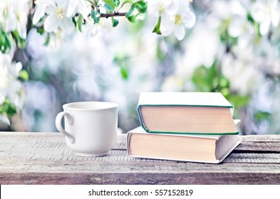 Cup hot coffee or tea, cocoa, chocolate and book outdoors on wooden table or bench in sunny weather on spring season background. Return to spring or summer time. Pile of books and cup in nature.