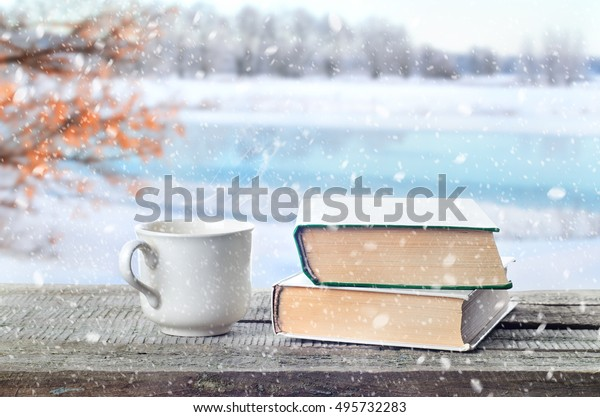 Cup hot coffee or tea, cocoa, chocolate and book outdoors on wooden table or bench in snowy weather on winter season background. Return to winter time. Pile of books and cup in nature.