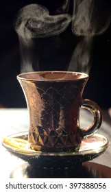 Cup of hot coffee or tea  with steam on dark background.