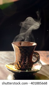 Cup of hot coffee or tea  with steam on dark background. The snake of smoke.