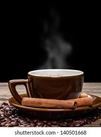 Cup of hot drink with coffee beans