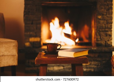 Cup of hot drink in front of warm fireplace