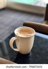 A cup of hot drink with froth on top of marble table in portrait