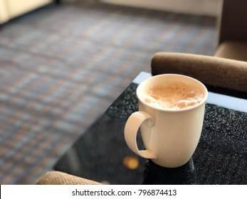 Cup of hot drink with froth on top of marble table in landscape