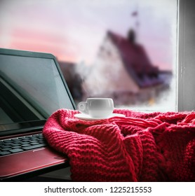 cup with a hot drink and laptop for on the windowsill in the background of a winter city