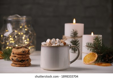 Cup of hot drink with marshmallows and cookies on white table
