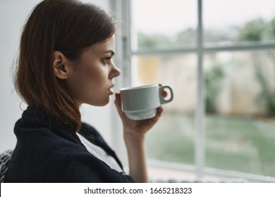 cup with hot drink and women near the window