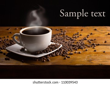cup of hot espresso with coffee beans on dark wooden background