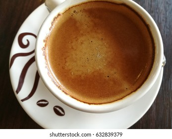 Cup of hot espresso coffee on wooden table