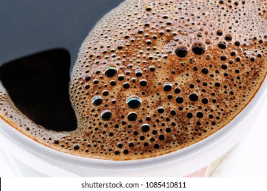 Cup of hot fresh coffee macro closeup as a background. Top view cup of coffee isolated on white background.