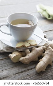 Cup of hot ginger tea with ginger slices and ginger root, vertical orientation.