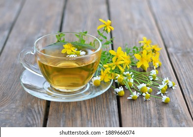 Cup of hot herbal tea from St John's wort and Matricaria chamomilla on a wooden table close-up. Concept of a healthy lifestyle.
