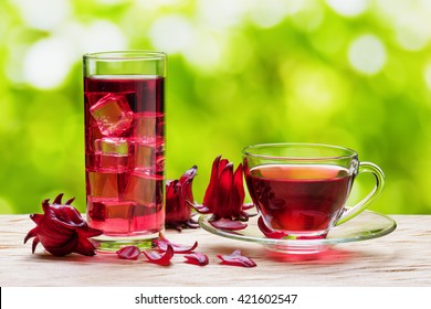 Cup of hot hibiscus tea (karkade, red sorrel, Agua de flor de Jamaica) and the same cold drink with ice in glass on nature background. Drink made from magenta calyces (sepals) of roselle flowers.