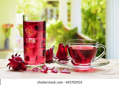 Cup of hot hibiscus tea (karkade, Agua de flor de Jamaica) and the same cold drink with ice cubes in glass on wooden table at terrace. Drink made from magenta calyces (sepals) of roselle flowers.
