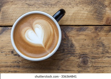Cup of hot latte art coffee on wooden table